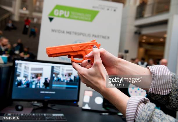 Sam Tkach of Deep Science holds a fake gun as he demonstrates the company's security system to automatically detect firearms and thieves to be used...