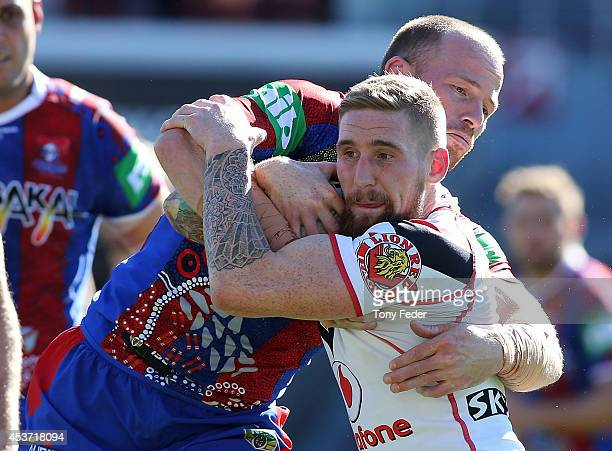 Sam Tomkins of the Warriors is tackled by the Knights defence during the round 23 NRL match between the Newcastle Knights and the New Zealand...