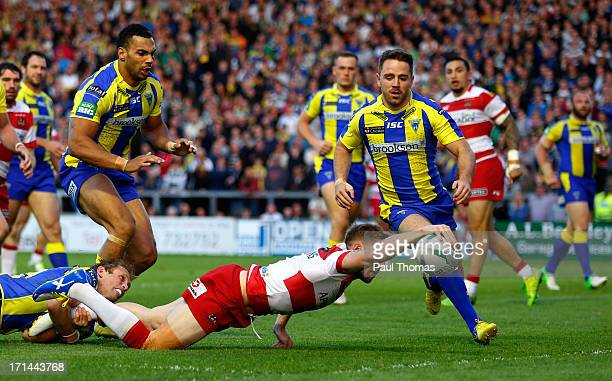 Sam Tomkins of Wigan dives over to score a try in the tackle of Warrington's Brett Hodgson during the Super League match between Warrington Wolves...