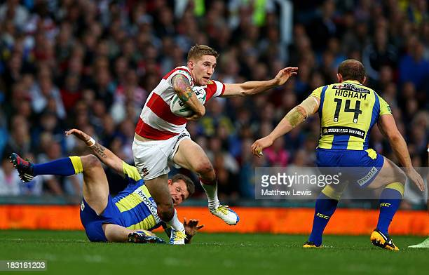 Sam Tomkins of Wigan goes past Lee Briers and Micky Higham of Warrington during the Super League Grand Final between Warrington Wolves and Wigan...