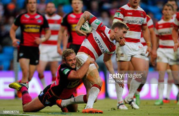 Sam Tomkins of Wigan is tackled by Paul McShane of Leeds during the Super League Magic Weekend match between Leeds Rhinos and Wigan Warriors at the...