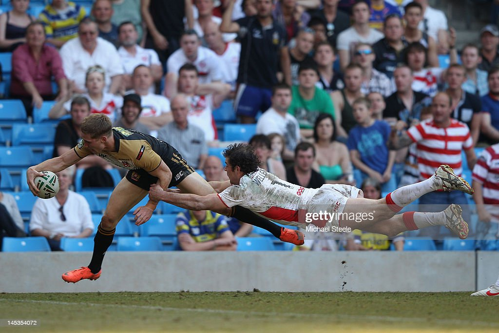 Sam Tomkins (L) of Wigan Warriors scores a try as Paul Wellens (R) of St Helens dives in vain during the Stobart Super League 'Magic Weekend' match between St Helens and Wigan Warriors at the Etihad Stadium on May 27, 2012 in Manchester, England.