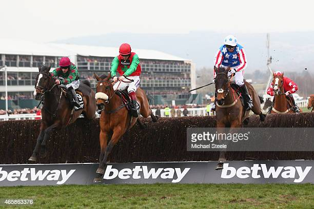 Sam TwistonDavies riding Dodging Bulletts clears the last fence to win the Betway Queen Mother Champion Steeple Chase from Brian Hughes riding...