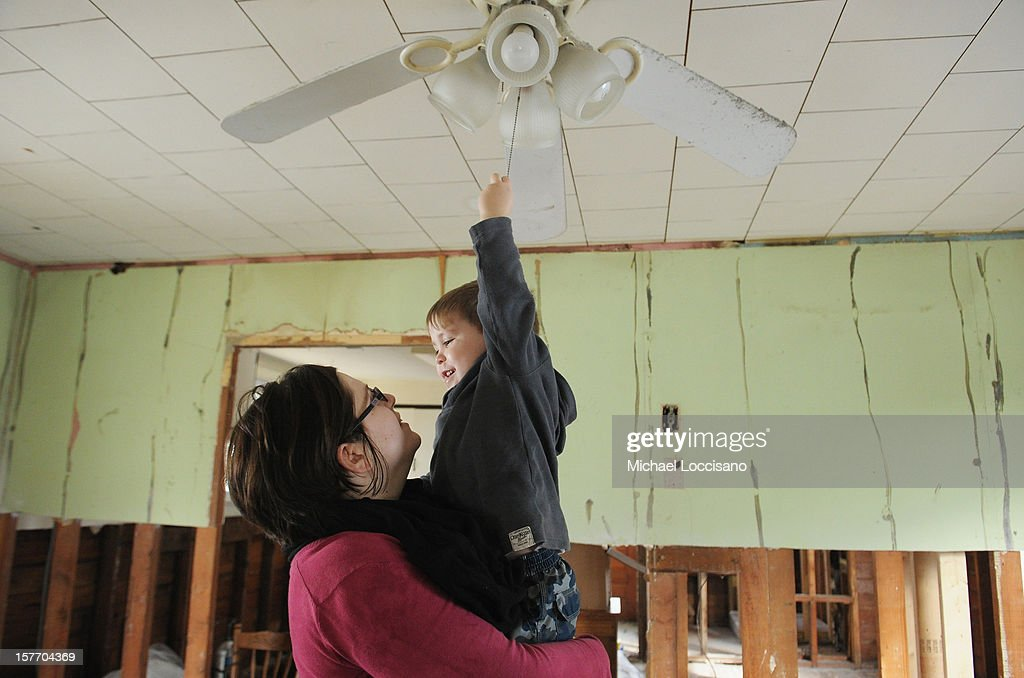 Sam Van Rikxoort (L) and her son Kaiden Van Rikxoort visit their home devastated by Superstorm Sandy a month prior on December 5, 2012 in Union Beach, New Jersey. With a population of 6,200, roughly 1,000 homes were flooded and 200 rendered inhabitable.
