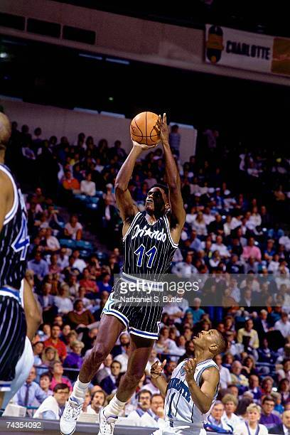 Sam Vincent of the Orlando Magic shoots against Mugsy Bogues of the Charlotte Hornets during a game played in 1991 at the Charlotte Coliseum in...
