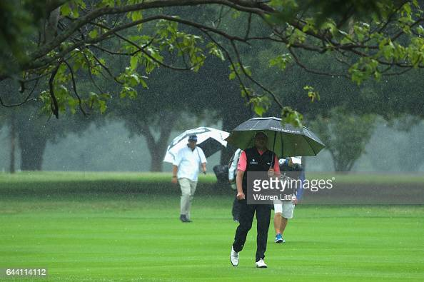 Sam Walker of England walks up the 18th fairway as the rain falls during the first round of the Joburg Open at Royal Johannesburg and Kensington Golf...