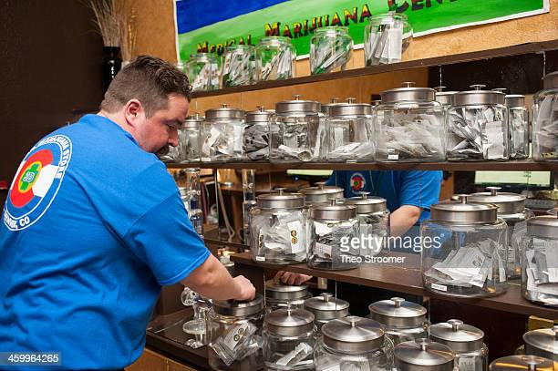 Sam Walsh a budtender sets up marijuana products as the 3D Denver Discrete Dispensary prepares to open for retail sales on January 1 2014 in Denver...