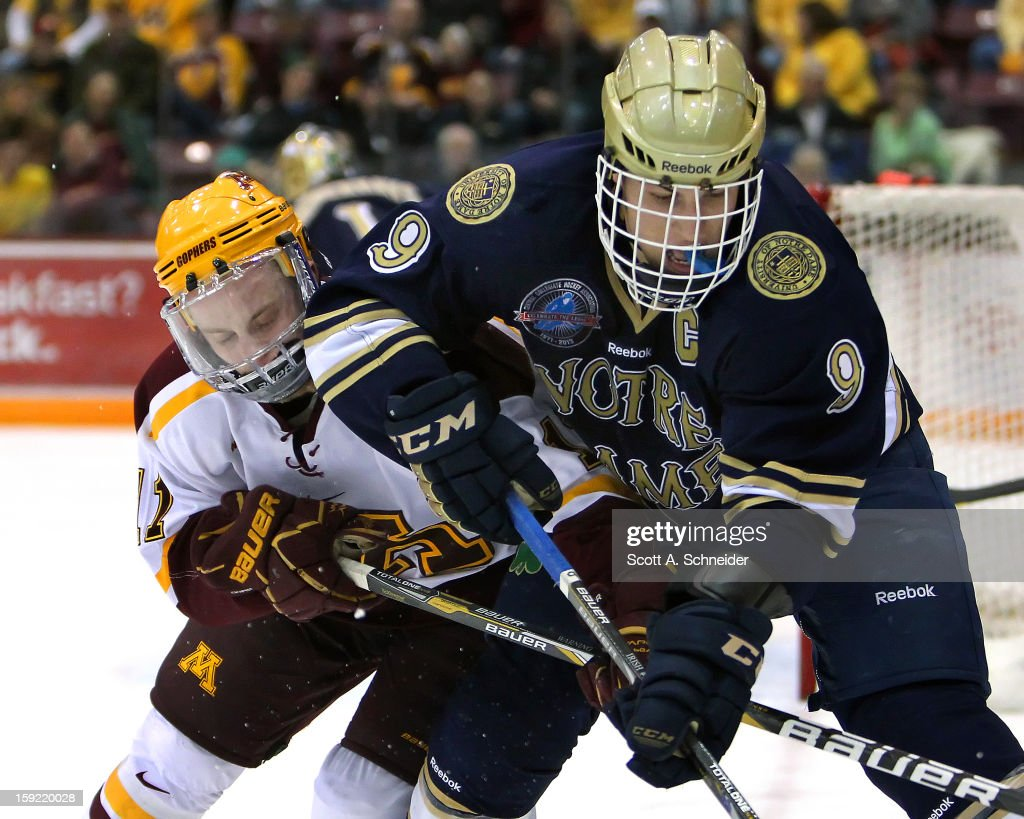 Sam Warning #11 of the Minnesota Gophers battles to the puck with Anders Lee #9 of the Notre Dame Fighting Irish January 8, 2013 at Mariucci Arena in Minneapolis, Minnesota.