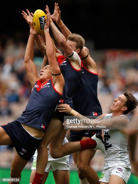 Sam Weideman of the Demons marks ahead of teammates Mitch Hannan and Max Gawn as Harrison Macreadie of the Blues looks on during the 2017 AFL round...