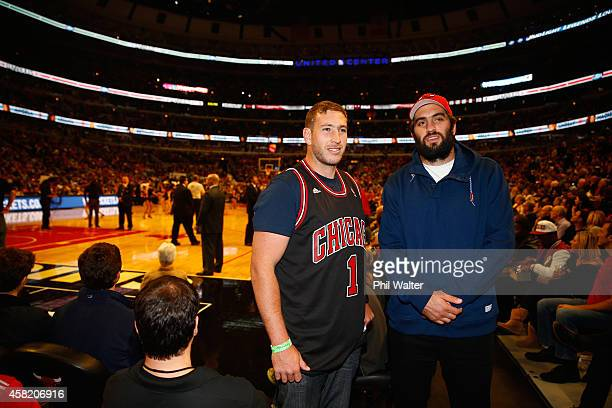 Sam Whitelock and Luke Romanos of the All Blacks stand courtside as they attend the Chicago Bulls v Cleveland Cavaliers NBA game at the United Center...