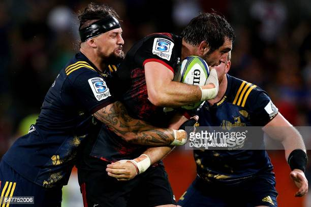Sam Whitelock of the Crusaders tries to break the tackle of Elliot Dixon of the Highlanders during the round two Super Rugby match between the...