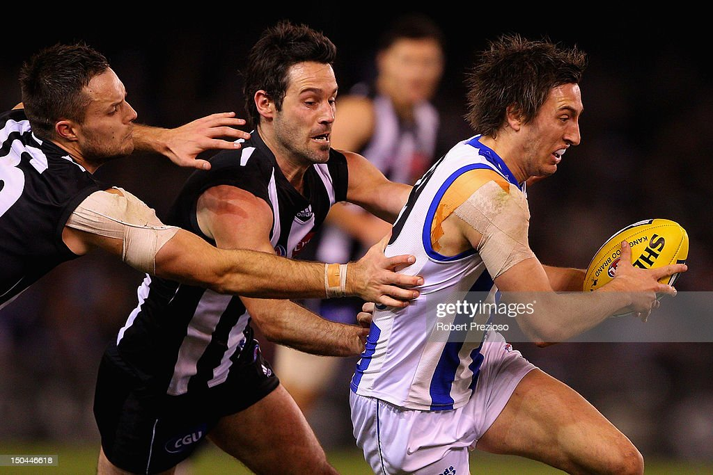Sam Wright of the Kangaroos is tackled by Alan Didak of the Magpies during the round 21 AFL match between the Collingwood Magpies and the North Melbourne Kangaroos at Etihad Stadium on August 18, 2012 in Melbourne, Australia.