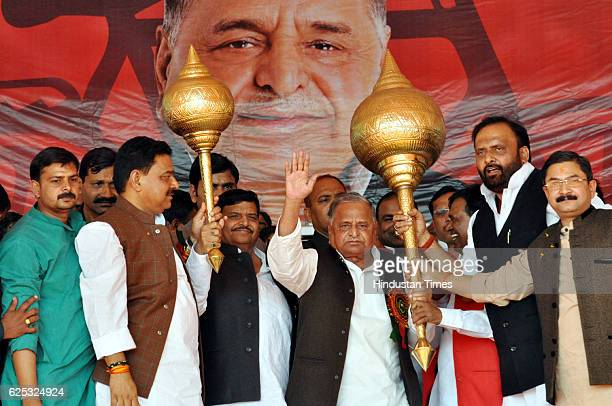 Samajwadi Party Chief Mulayam Singh Yadav and his brother Shivpal Singh Yadav lifting mace presented by party workers during a campaign rally at...