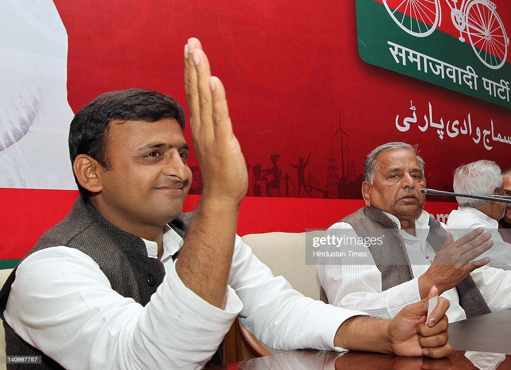 Samajwadi Party chief Mulayam Singh Yadav sits with his son Akhilesh Yadav at press conference at the party office on March 9 2012 in Lucknow India...