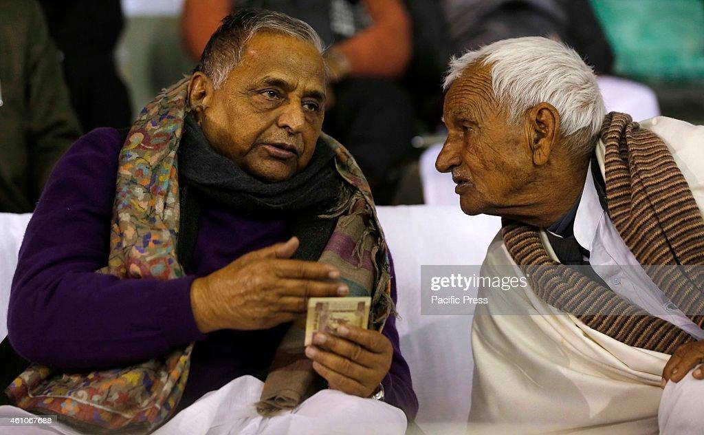 Samajwadi Party Supremo Mulayam Singh Yadav talks with a man during Saifai Mahotsav in Saifai village in Etawah district in the northern Indian state...