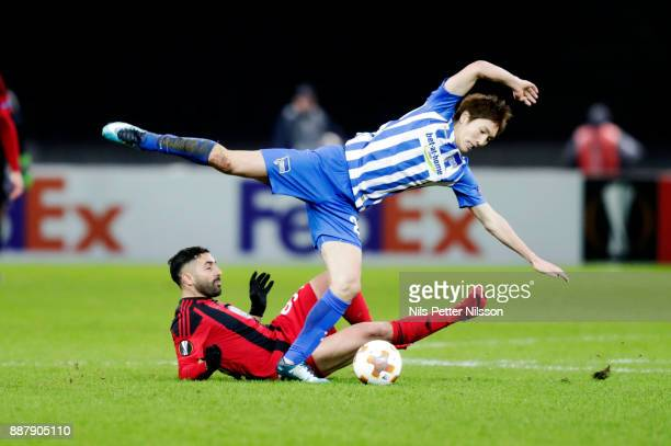 Saman Ghoddos of Ostersunds FK trips Genki Haraguchi of Hertha Berlin SC during the UEFA Europa League group J match between Hertha BSC and...