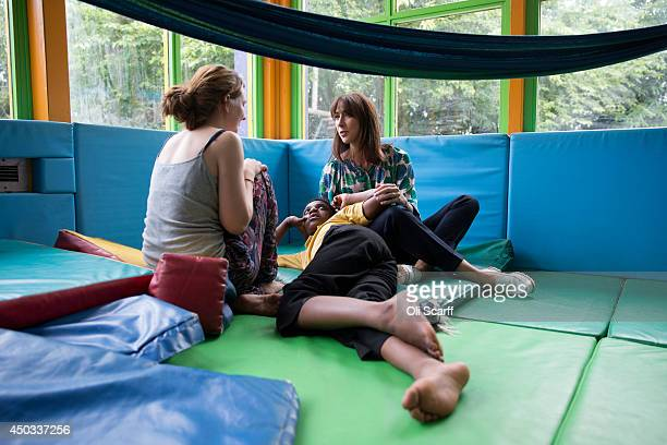 Samantha Cameron the wife of British Prime Minster David Cameron speaks with playworker Paige and 11 yearold Nathaniel Restal who has ASD as she...