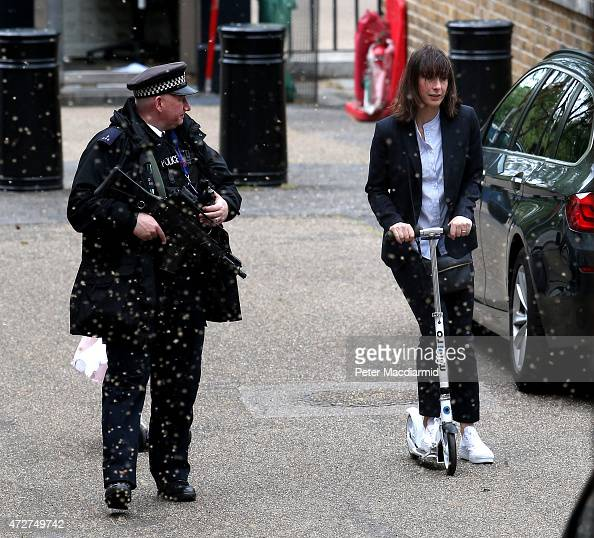 Samantha Cameron wife of Prime Minister David Cameron is watched by an armed policeman as she rides a scooter at the back entrance to number 10...
