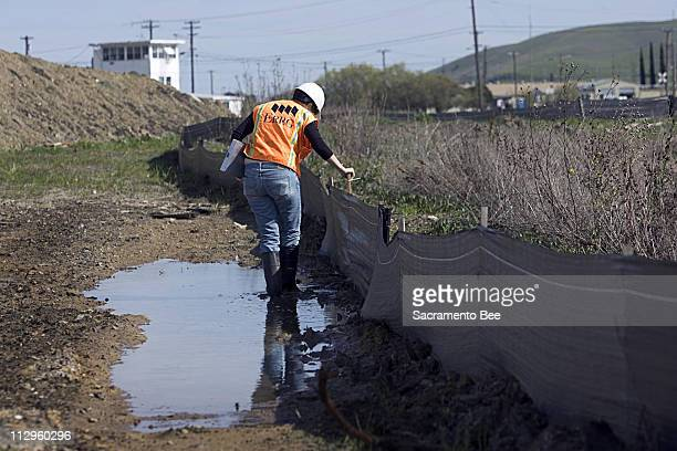 Samantha CaruthersKnight a geologist with the Engineering/Remediation Resources Group of Concord inspects a barrier installed at the Concord Naval...