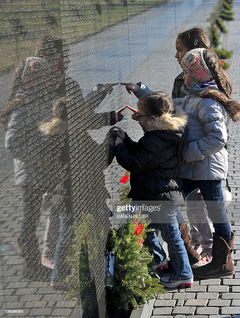Samantha Hughes(C), her sister Hailey(top) and Isabella Santucci(Bottom) look at names engraved in the Vietnam Veterans Memorial Wall December 19, 2011 in Washington, DC. The Vietnam Veterans Memorial Fund (VVMF) Honored veterans and active-duty military personnel during its 15th Annual Christmas Tree Ceremony at The Wall. AFP PHOTO/Karen BLEIER