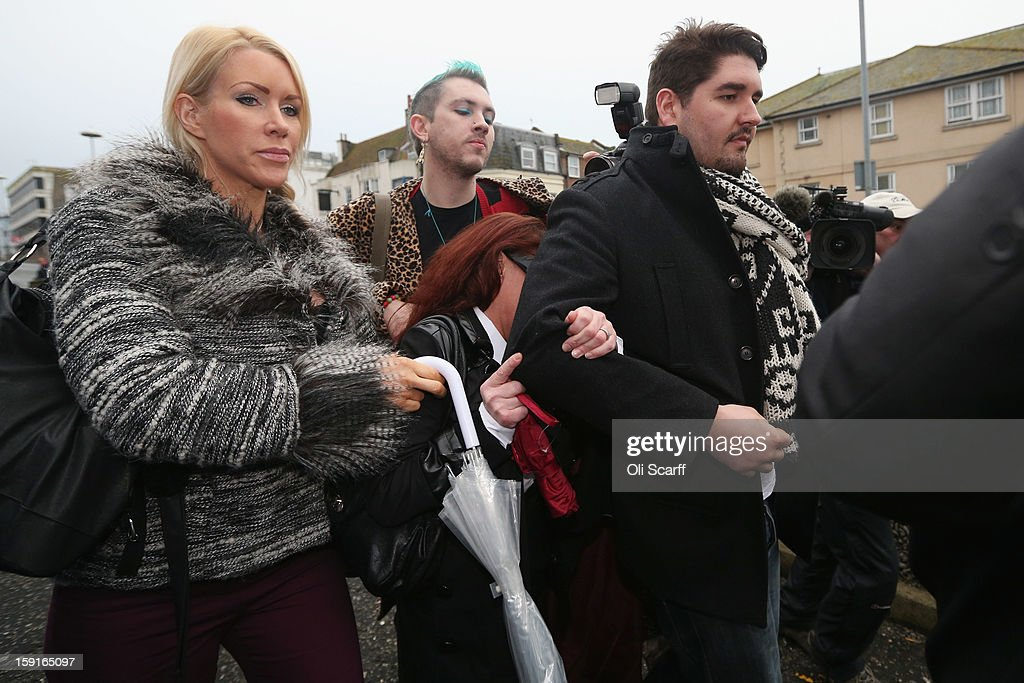 Samantha Kidd (C), the estranged wife of former stuntman Eddie Kidd, is shielded from view by friends as she leaves Brighton Magistrates Court charged with assaulting Mr Kidd on January 9, 2013 in Brighton, England. Mrs Kidd is accused of assaulting Mr Kidd, who is paralysed and brain-damaged after a stunt went wrong in August 1996, six times over a period of four months from July to October 2012.