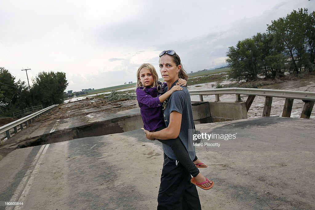 Samantha Kinzig of Longmont, Colorado and her five year-old daughter Isabel take in a closer view of a damaged bridge on Weld County Road 1 on September 13, 2013 in Longmont, Colorado. Heavy rains for the better part of week have fueled widespread flooding in numerous Colorado towns. Kinzig is a Colorado native who says she's never seen anything like this.