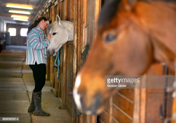 Samantha Mamaty pets Vail at the Herring Brook Farm horse stall as Q looks on in Pembroke MA on Mar 15 2017 Many horses are bordered at the farm...