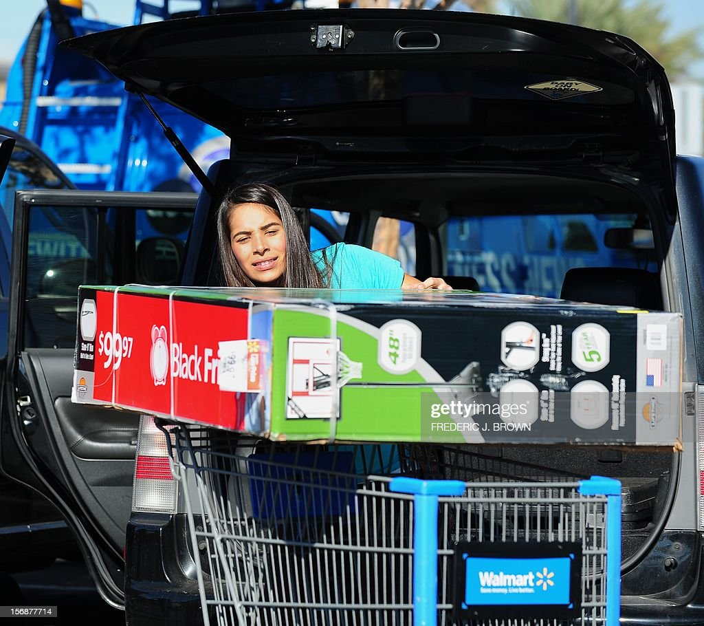 Samantha Ortiz struggles to put a newly purchased basketball hoop set from Walmart into her vehicle as Walmart employees and their supporters protested nearby in Paramount, California on November 23, 2012. Unhappy Walmart employees are protesting across the US, seeking to make their demands for better pay and benefits more visible to the Americans flocking to the Black Friday shopping frenzy. AFP PHOTO / Frederic J. BROWN