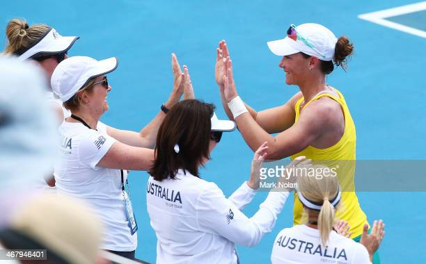 Samantha Stosur of Australia celebrates with the Australian bench after winning her singles match against Victoria Kan of Russia during the Fed Cup...