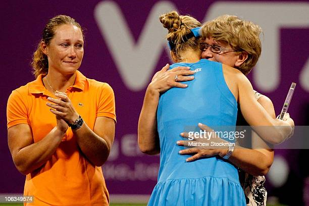 Samantha Stosur of Australia looks on as Elena Dementieva of Russia is embraced by her mother Vera Dementieva after announcing her retirement after...