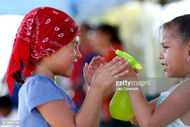 Samantha Tlaxcalteco left of Winnetka is sprayed with cold water by her friend Cynthia Torres of Conoga Park while their siblings play in a Project...