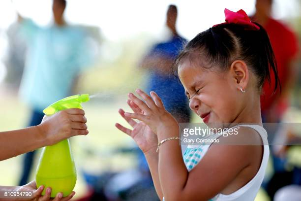 Samantha Tlaxcalteco left of Winnetka sprays her friend Cynthia Torres of Conoga Park with cold water while their siblings play in a Project 2000...