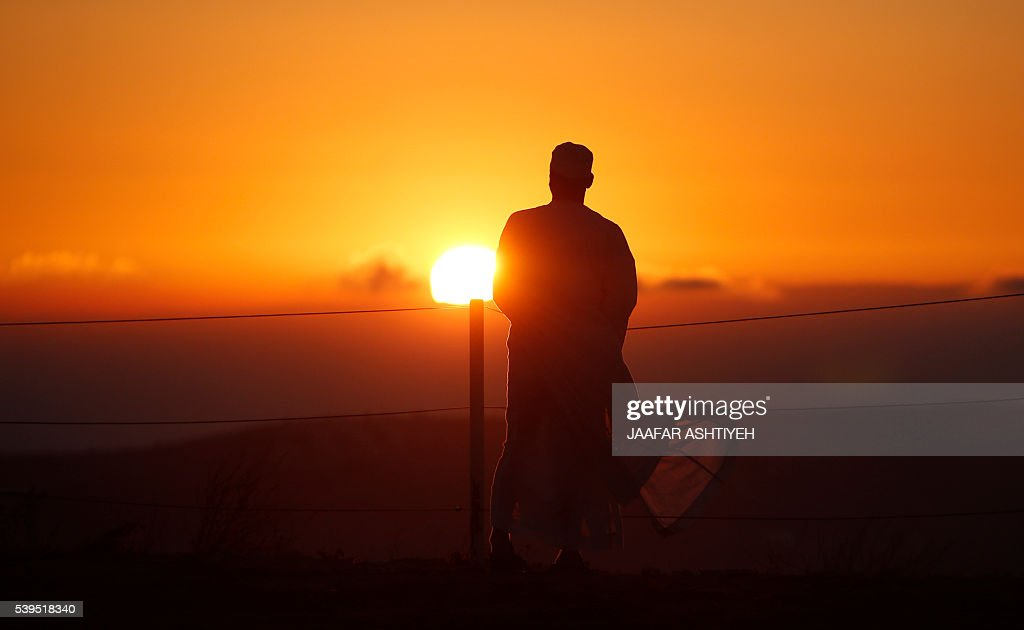 A Samaritan watches the sun rising as worshipers gather to pray on top of Mount Gerizim near the northern West Bank city of Nablus to celebrate the...