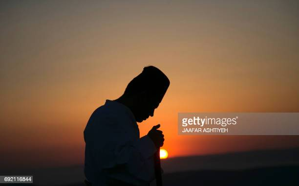 A Samaritan worshiper prays on top of Mount Gerizim near the northern West Bank city of Nablus as they celebrate the Shavuot festival at dawn on June...