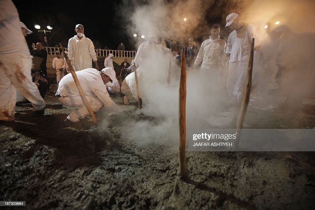 Samaritans take part in the traditional Passover sacrifice ceremony, where sheep and goats are slaughtered and then baked, at Mount Gerizim near the northern West Bank city of Nablus on April 23, 2013. The Israeli Samaritan community which numbers about 720 people practice a religion that is based on four principles of faith, one God - the God of Israel; one Prophet - Moses Ben Amram; the belief in the Torah - the first five books of the Bible and one holy place - Mount Gerizim, close to Tel Aviv in Israel. AFP PHOTO/JAAFAR ASHTIYEH
