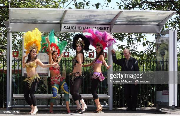 Samba dancers Gillian Harkness Thraissa Luna Fiona Hay and Georgina Anderson from dance troupe Eletricat entertain a man waiting at a bus stop in...