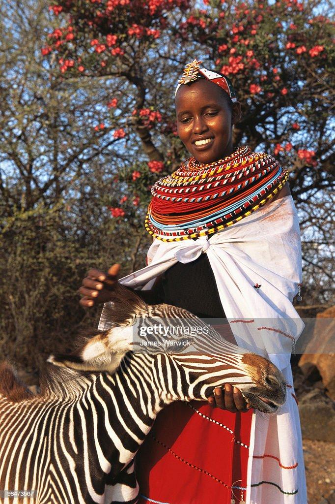 Samburu woman with orphaned Grevy's zebra foal : Stock Photo