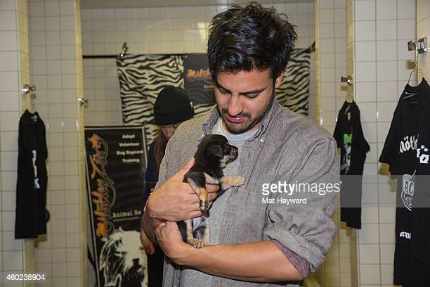Sameer Gadhia of Young The Giant holds a pupppy brought by Motley Zoo Animal Rescue backstage during Deck the Hall Ball hosted by 1077 The End at...