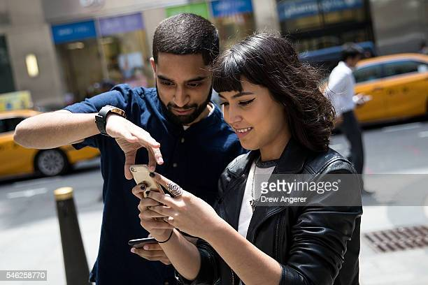 Sameer Uddin and Michelle Macias play Pokemon Go on their smartphones outside of Nintendo's flagship store July 11 2016 in New York City The success...