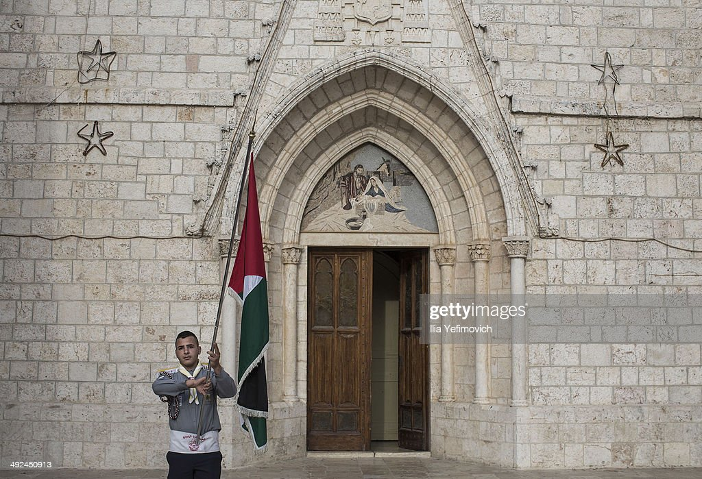 Samer M. Jarad of the Latin Christian church scout brigade holding a Palestinian flag and poses for a portrait outside the church on May 20, 2014 in Bethlehem, West Bank. The scouts will act as ushers when Pope Francis makes his first visit to the Holy Land as pontiff to both the West Bank and Israel this coming Sunday. The Pope will celebrate two public Masses during his visit, one in Amman, Jordan and the other in Manger Square in Bethlehem.