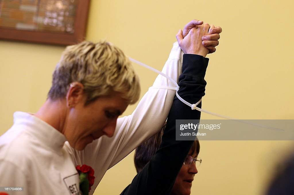 A same-sex couple hold up their bound hands after they were arrested by San Francisco sheriffs deputies for staging a sit-in protest after same-sex couples were denied marriage licenses from the San Francisco county clerk on February 14, 2013 in San Francisco, California. Close to a dozen same-sex couples who were denied marriage licenses were arrested after they staged a sit-in demonstration inside the office of San Francisco's county clerk.