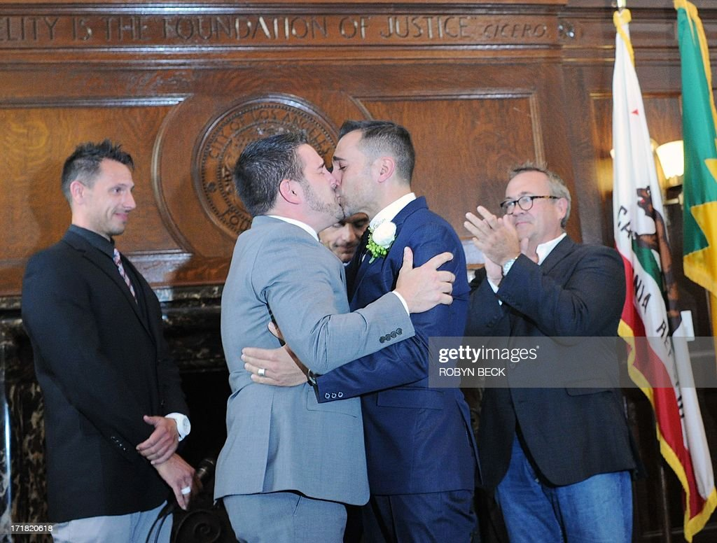 Same-sex couple Paul Katami (L) and Jeff Zarrillo (2nd-L) kiss after they are officially married by Los Angeles Mayor Antonio Villaraigosa at Los Angeles City Hall June 28, 2013, becoming one of the first gay couples to marry in California since the Supreme Court refused to rule on Proposition 8 on June 26.