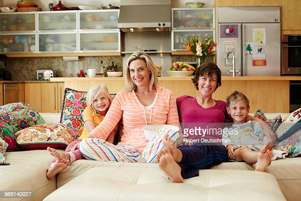 Same-sex couple sitting in house with kids.