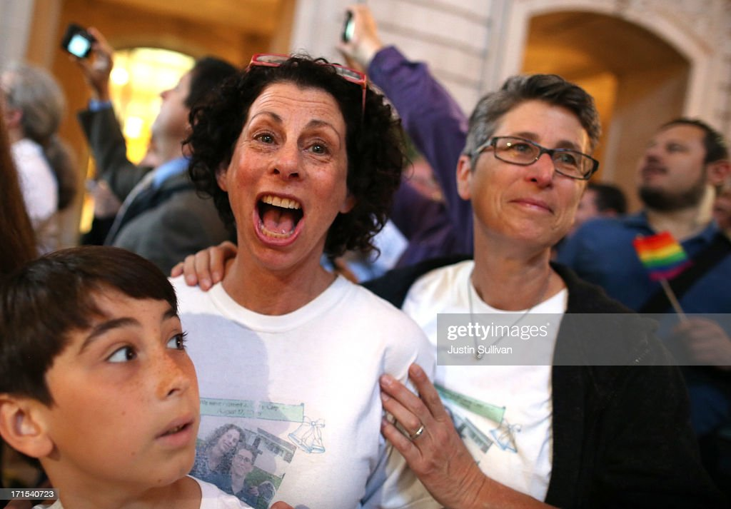 Same-sex couple Sue Rochman (C) and Robin Romdalvik (R) with their son Maddox Rochman-Romdalvik celebrate upon hearing the U.S. Supreme Court's rulings on gay marriage in City Hall June 26, 2013 in San Francisco, United States. The high court struck down the Defense of Marriage Act (DOMA) and ruled that supporters of California's ban on gay marriage, Proposition 8, could not defend it before the Supreme Court.