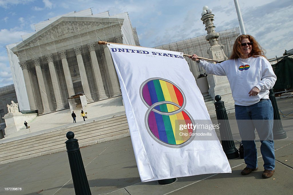 Same-sex marriage proponent Kat McGuckin of Oaklyn, New Jersey, holds a gay marriage pride flag while standing in front of the Supreme Court November 30, 2012 in Washington, DC. With the Supreme Court building draped in a photo-realistic sheet during a repair and preservation project, the justices met today to consider hearing several cases dealing with the rights of gay couples who are married, want to get married or are in domestic partnerships.