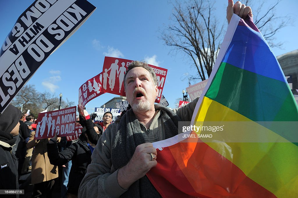 A same-sex marriage supporter (C) holds up a flag among anti-gay protesters in front of the US Supreme Court on March 26, 2013 in Washington, DC. The US Supreme Court on Tuesday takes up the emotionally charged issue of gay marriage as it considers arguments that it should make history and extend equal rights to same-sex couples. Waving US and rainbow flags, hundreds of gay marriage supporters braved the cold to rally outside the court along with a smaller group of opponents, some pushing strollers. Some slept outside in hopes of witnessing the historic hearing. AFP PHOTO/Jewel Samad