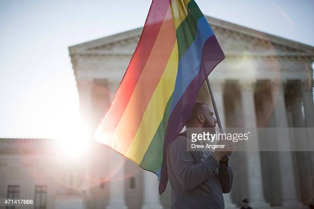 Samesex marriage supporter Vin Testa of Washington DC holds a rainbow pride flag near the Supreme Court April 28 2015 in Washington DC On Tuesday the...