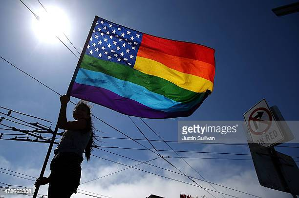 A samesex marriage supporter waves a pride flag while celebrating the US Supreme Court ruling regarding samesex marriage on June 26 2015 in San...