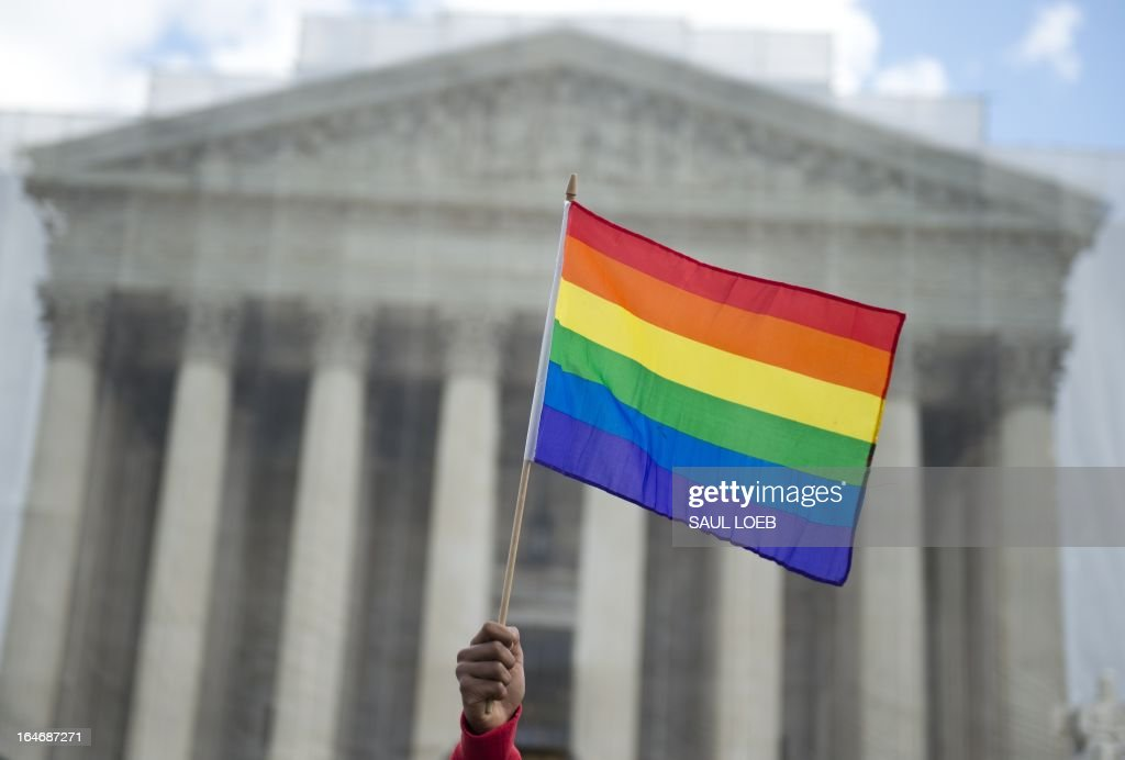 A same-sex marriage supporter waves a rainbow flag in front of the US Supreme Court on March 26, 2013 in Washington, DC, as the Court takes up the issue of gay marriage. The US Supreme Court on Tuesday heard arguments on the emotionally charged issue of gay marriage as it considers arguments that it should make history and extend equal rights to same-sex couples. Waving US and rainbow flags, hundreds of gay marriage supporters braved the cold to rally outside the court along with a smaller group of opponents, some pushing strollers. Some slept outside in hopes of witnessing the historic hearing. AFP PHOTO / Saul LOEB