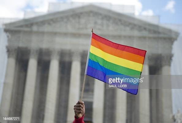 A samesex marriage supporter waves a rainbow flag in front of the US Supreme Court on March 26 2013 in Washington DC as the Court takes up the issue...